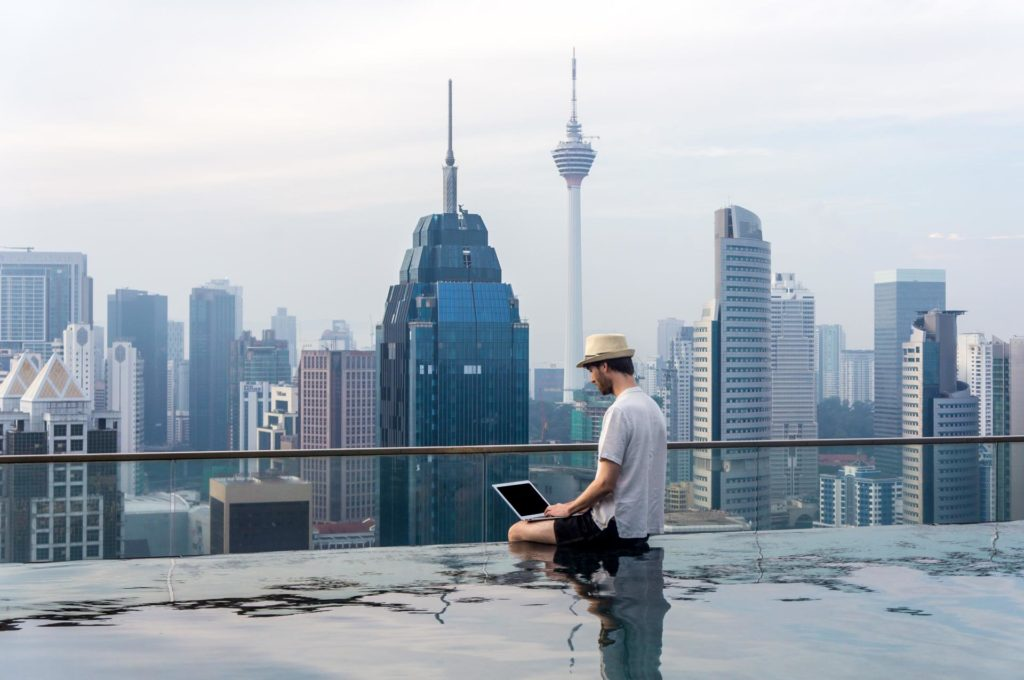 digital nomad in a pool on top of a building to make money while traveling
