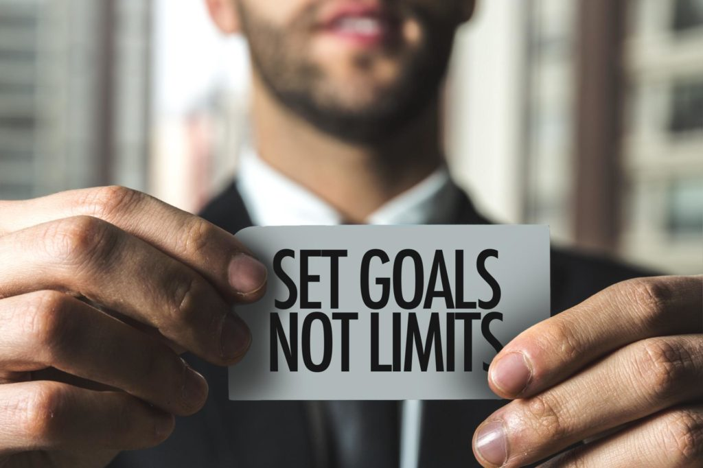 man holding card setting goals not limits