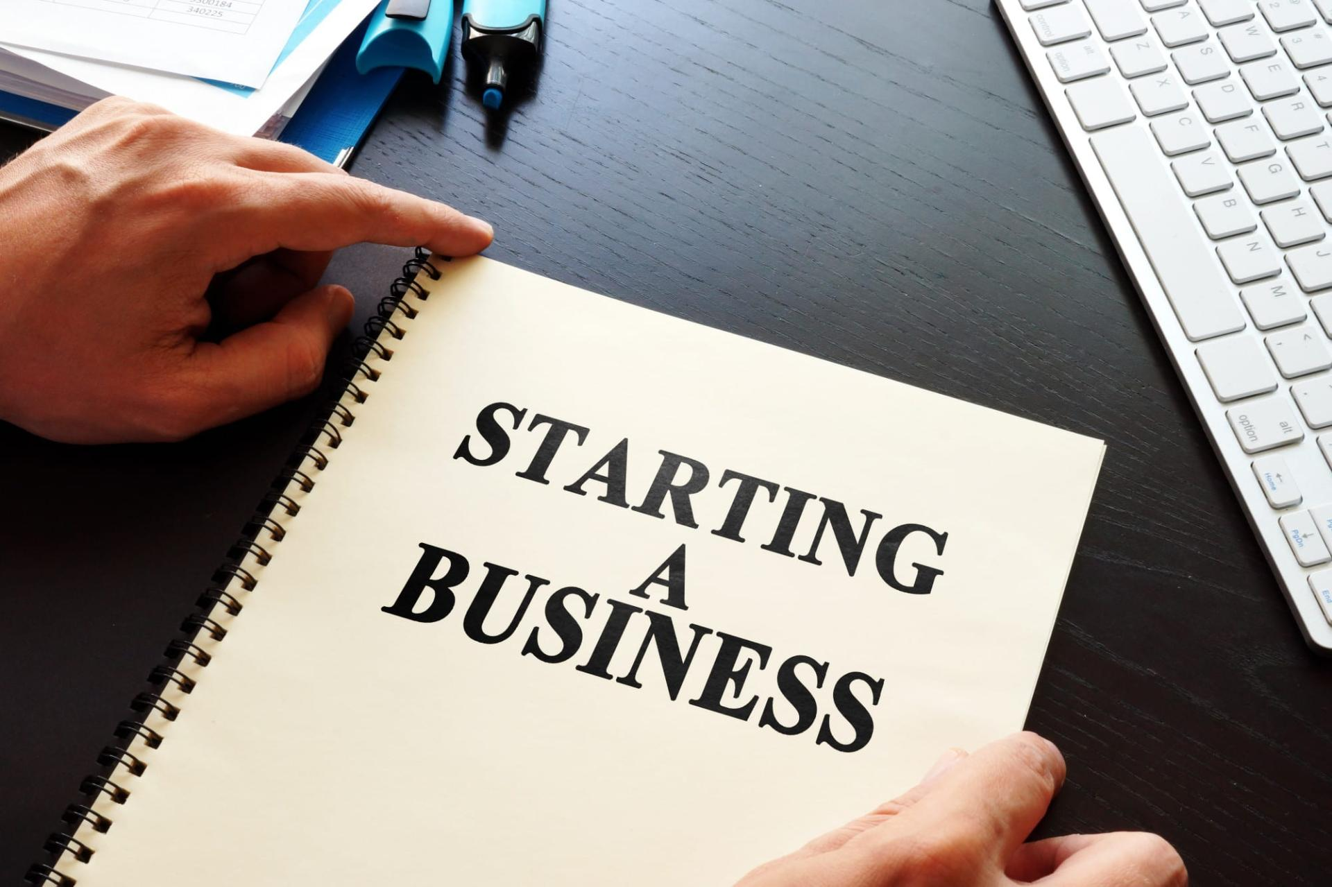 notebook with a text saying starting a business in small steps at a time