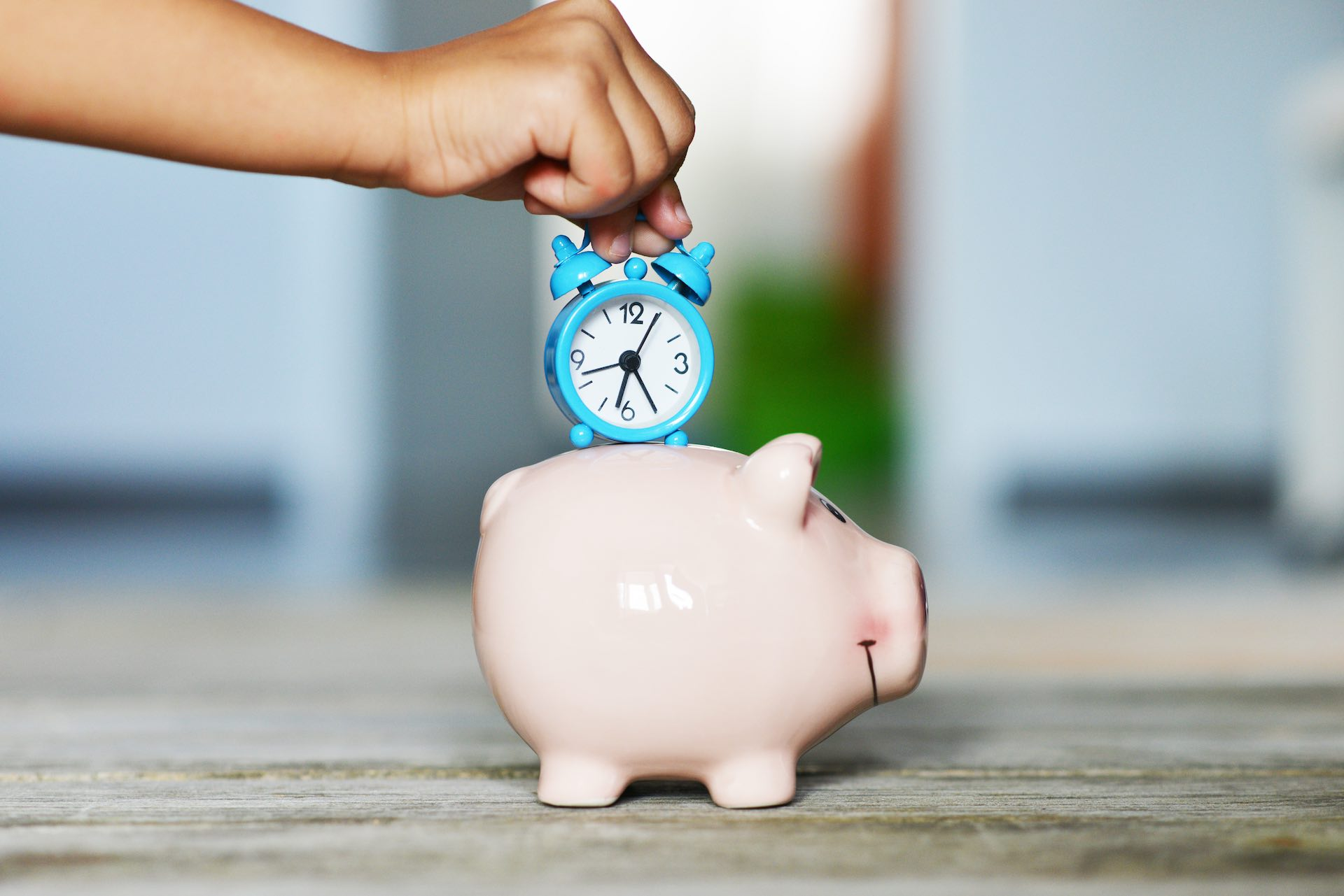 putting a clock on the piggy bank representing to save time