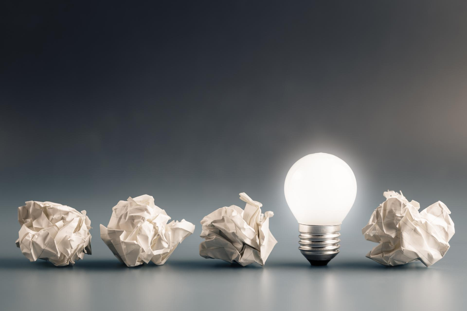 crumpled papers and a light bulb showing we need to fail for our success