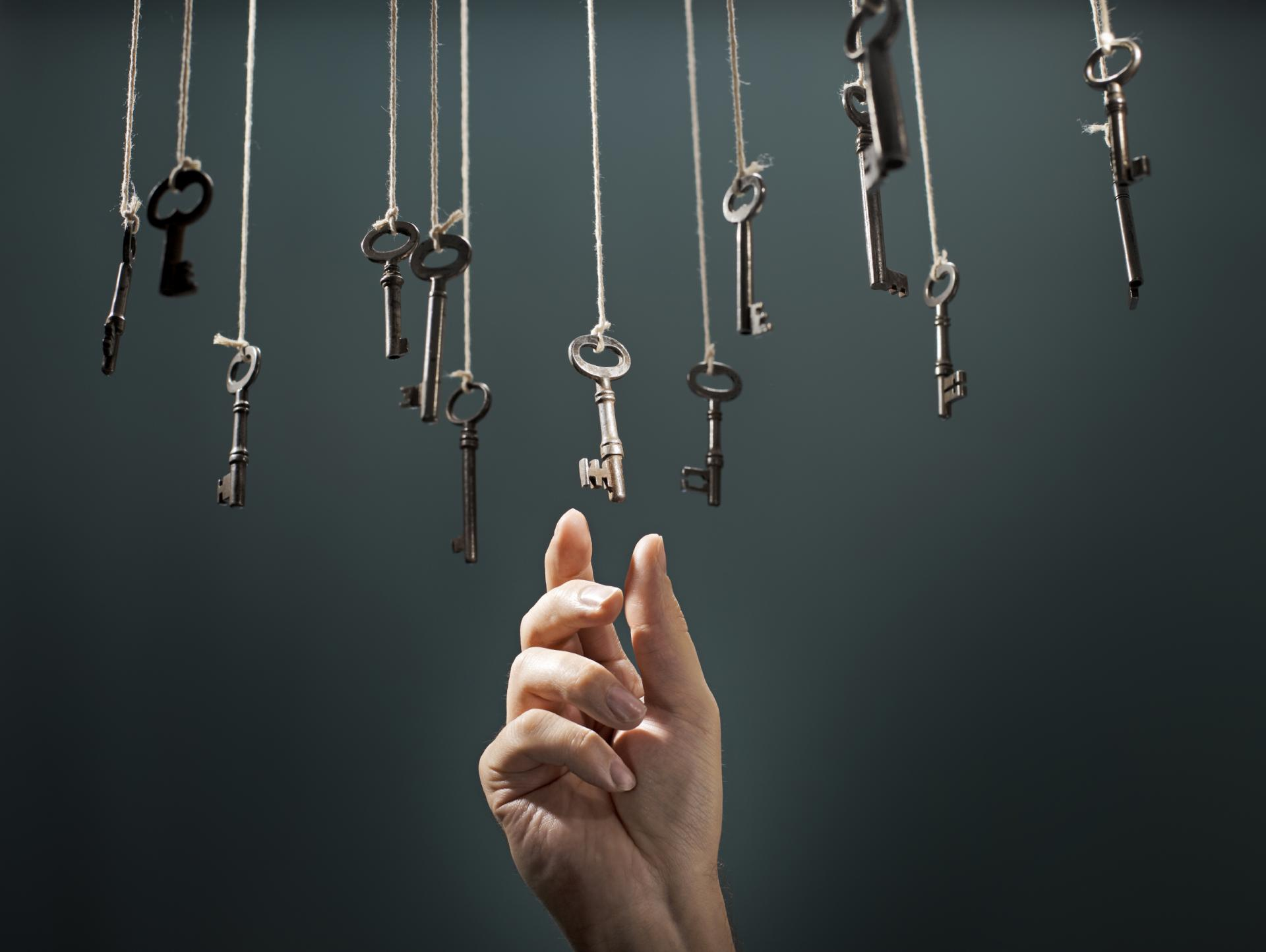 a hand choosing a hanging key listening to gut intuition