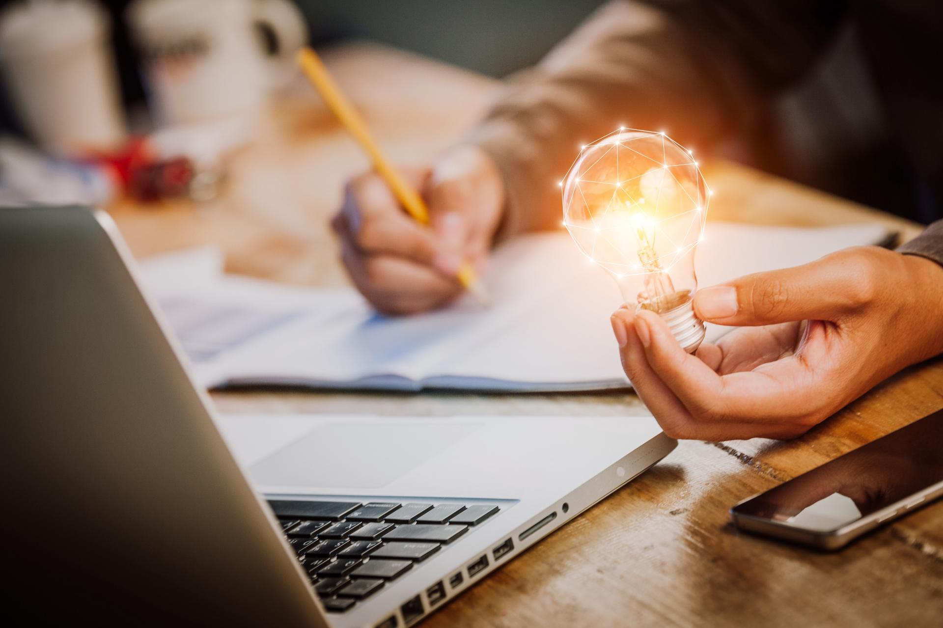 business man with awareness holding a lit light bulb and writing